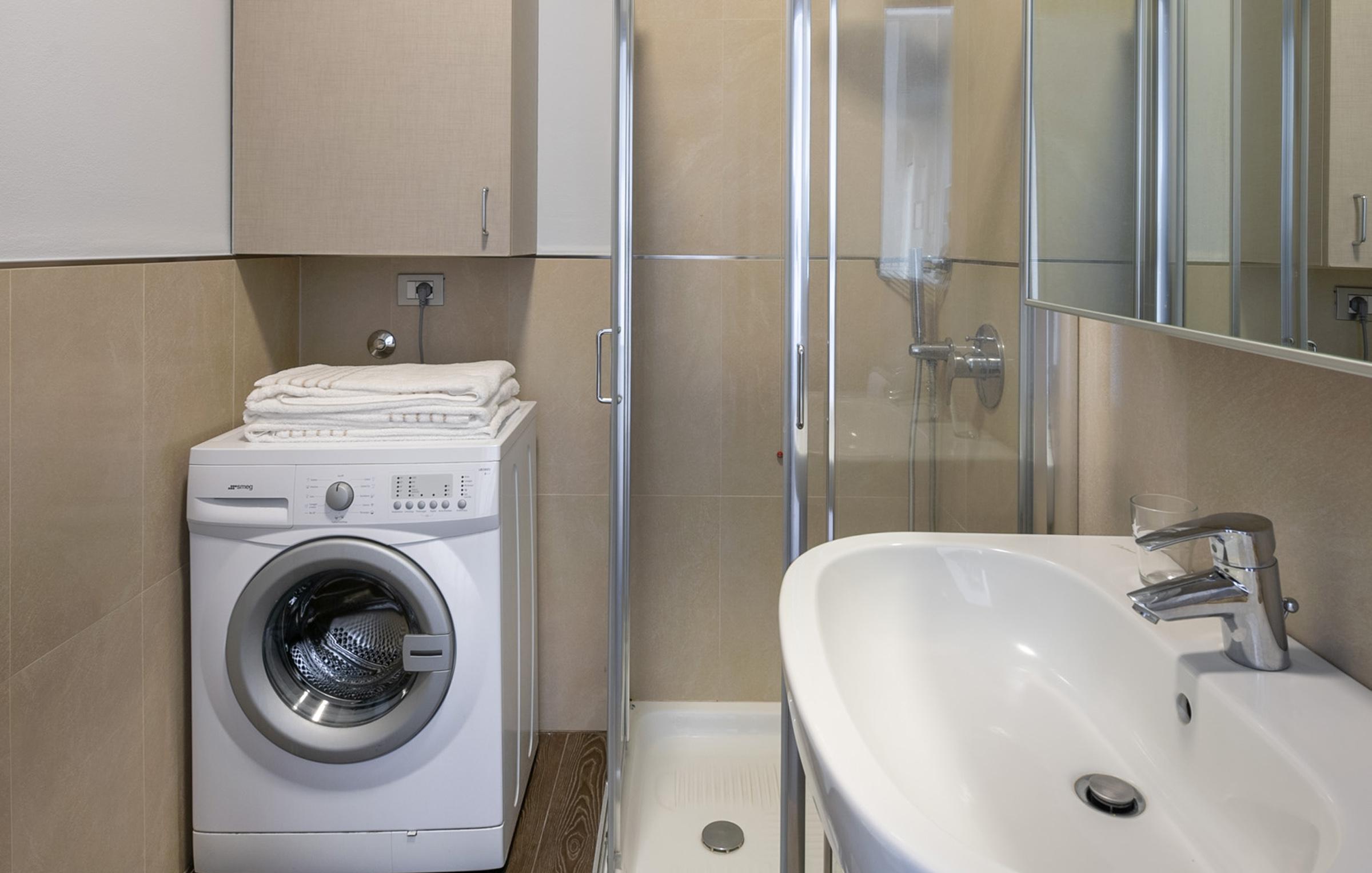 Il bagno degli appartamenti di Residenza Porta Volta a Milano ha doccia e lavatrice