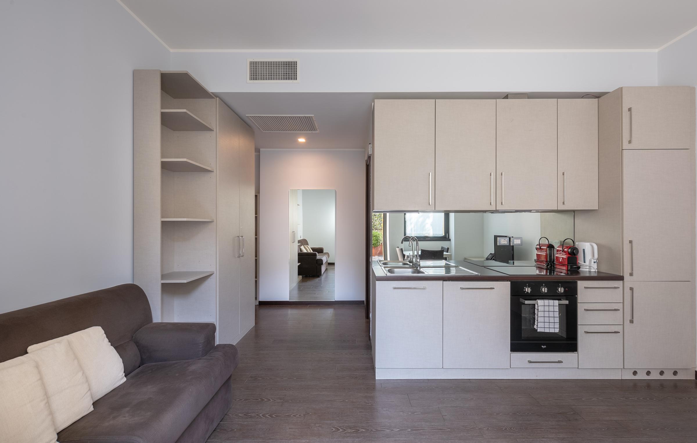 Divano letto, cucina attrezzata, tavolo con sedie, scrivania e angolo TV